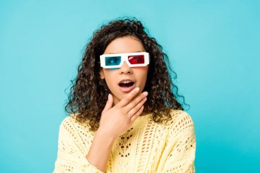 surprised curly african american woman in 3d glasses touching face isolated on blue