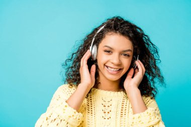 happy curly african american girl listening music in headphones and looking at camera isolated on blue