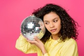 beautiful curly african american woman holding shiny disco ball isolated on crimson
