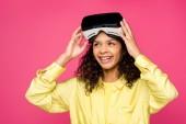 glücklich lockige afrikanisch-amerikanische Frau trägt Virtual-Reality-Headset und lächelt isoliert auf purpurrot