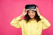 göndör afro-amerikai nő visel virtuális valóság fülhallgató és mosolyogva elszigetelt a bíbor
