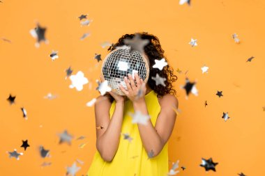 selective focus of african american girl in yellow dress covering face with disco ball near shiny confetti stars on orange