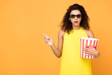 surprised curly african american woman holding popcorn bucket and pointing with finger isolated on orange
