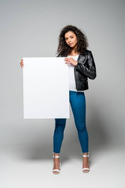 Beautiful curly african american woman holding blank placard while standing on grey stock vector