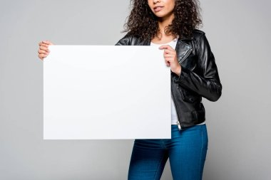 Cropped view of african american young woman holding blank placard isolated on grey stock vector