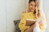 szép mosolygó fiatal nő olvasás könyvet ülve ablakpárkányon a másolási tér