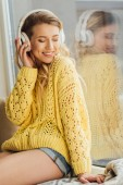 beautiful smiling young woman in headphones listening music at home