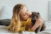 krásná dívka v pletených svetru ležela v posteli a hladila skotskou kočku