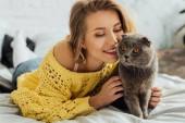 krásná usměvavá dívka v pletených svetru, co má doma rozkošný skotský kocour