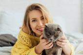 krásná usměvavá dívka v pletených svetru, jak se dívá na kameru a hubala skotskou kočku do postele