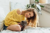 Photo beautiful smiling girl in knitted sweater hugging adorable scottish fold cat in bed at home
