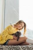 schöne lächelnde junge Frau umarmt schottische Faltkatze, während sie auf Fensterbank mit Kopierraum sitzt