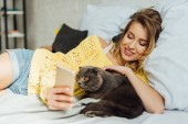 Photo beautiful smiling young woman using smartphone while lying in bed with scottish fold cat