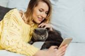 krásná mladá žena si vzala na telefon, zatímco ležela v posteli se skotskou kočkou