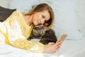 Photo beautiful young woman taking selfie on smartphone while lying in bed with scottish fold cat