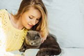 beautiful young woman in knitted sweater lying in bed and hugging scottish fold cat with copy space