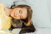 beautiful young woman with eyes closed lying in bed with adorable scottish fold cat