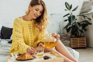 beautiful smiling girl in knitted sweater sitting and pouring tea in cup during breakfast in bedroom
