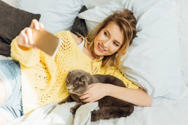 High angle view of beautiful young woman taking selfie on smartphone while lying in bed with scottish fold cat stock vector