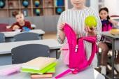 Ostříhané zobrazení školné dívky s zeleným jablkem a růžovým batohu ve třídě