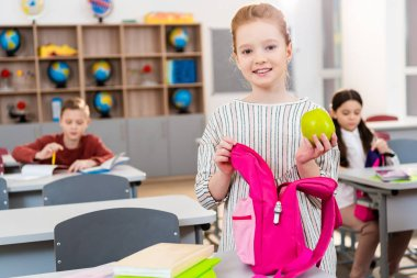 Smiling schoolgirl holding green apple and pink backpack in classroom