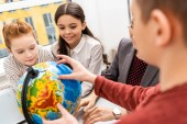 Oříznutý pohled žáků a učitelů na glóbus při studiu geografie ve třídě