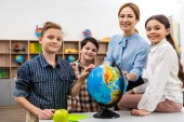 Teacher and pupils touching globe with smile while studying geography in classroom