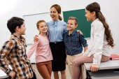 Laughing teacher embracing pupils in front of blackboard in classroom