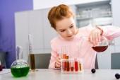 Lächelndes Schulmädchen mit Becher und chemischen Experimenten während des Chemieunterrichts
