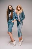 Blondýna a bruneta ženy v džínové oblečení s rukama v kapsách, s úsměvem a při pohledu na fotoaparát