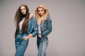 donna bionda e bruna in vestiti del denim con le mani in tasche che guarda lobbiettivo