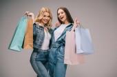 gyönyörű szőke és boldog barna női farmer ruha gazdaság bevásárló táskák, és mosolyogva