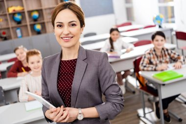 Smiling teacher with digital tablet standing in front of pupils and looking at camera