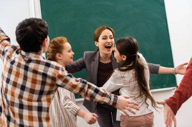 Happy pupils embracing teacher in front of blackboard in classroom