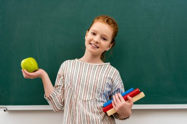 Cheerful ginger shoolgirl holding books and green apple in front of blackboard in classroom