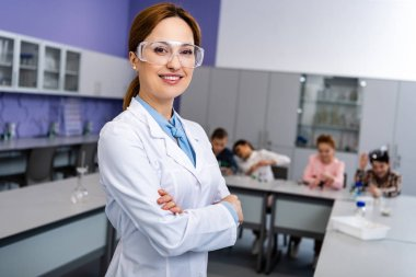 Smiling teacher in protective goggles standing with crossed arms in front of pupils during chemistry lesson