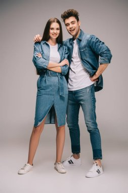 Attractive girlfriend in denim dress with crossed arms and smiling boyfriend in jeans and shirt hugging and looking at camera stock vector