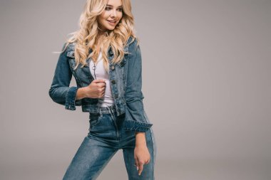 Attractive blonde woman in denim jacket and jeans smiling and looking away stock vector