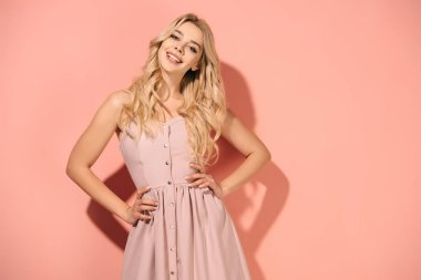 blonde and beautiful woman with hands on hips in pink dress smiling and looking at camera
