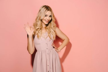 attractive and blonde woman in pink dress with hand on hip showing okay