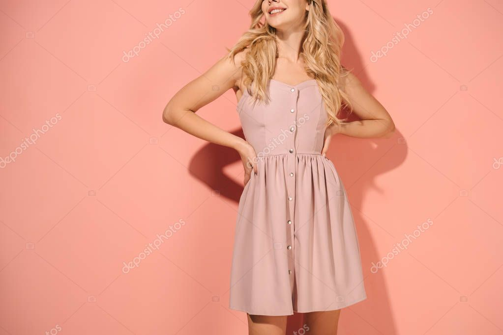 Cropped view of blonde woman with hands on hips in pink dress on pink background stock vector