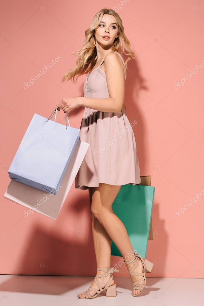 Attractive and blonde woman in pink dress with shopping bags looking away stock vector