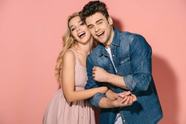 Smiling girlfriend in pink dress and handsome boyfriend in denim shirt hugging stock vector