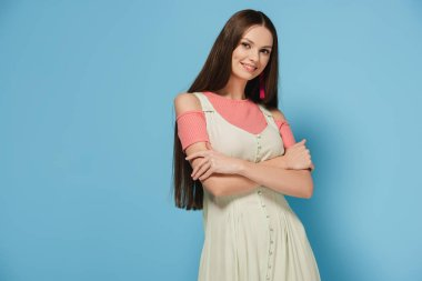 attractive and brunette woman in elegant dress with crossed arms looking at camera