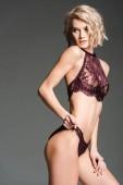 Fotografia bella ragazza sexy in lingerie Bordeaux in posa isolata su grigio