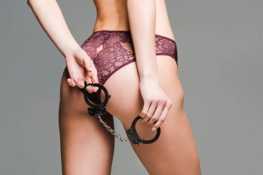 back view of sexy girl in burgundy lingerie posing with handcuffs isolated on grey