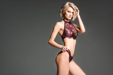 beautiful sexy girl in burgundy lingerie looking at camera and posing isolated on grey with copy space