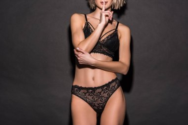 cropped view of sexy girl in lace lingerie showing silent gesture and posing on black