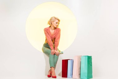 güzel şık kız sarı daire üzerinde alışveriş çantaları yakın oturan ve beyaz üzerinde poz