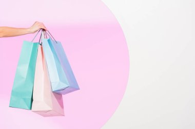 cropped view of young woman holding colorful shopping bags on white with pink circle